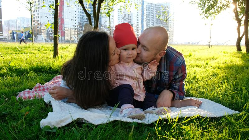 Happy family lies on grass in summer park. Parents kiss a little baby girl on the cheeks on both sides stock photo
