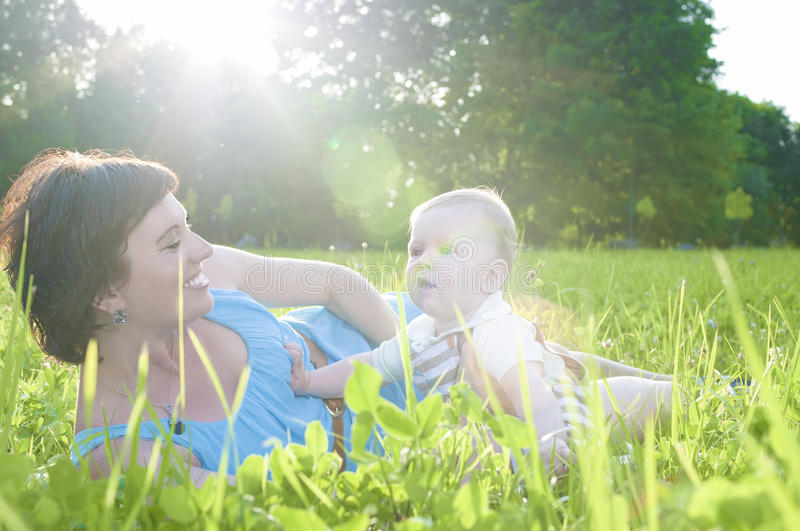 Happy Family Life Concepts and Ideas. Caucasian Brunette Mother with Her Toddler Son Spending Time Together. Outdoors Embraced in Park. Horizontal Image royalty free stock photography