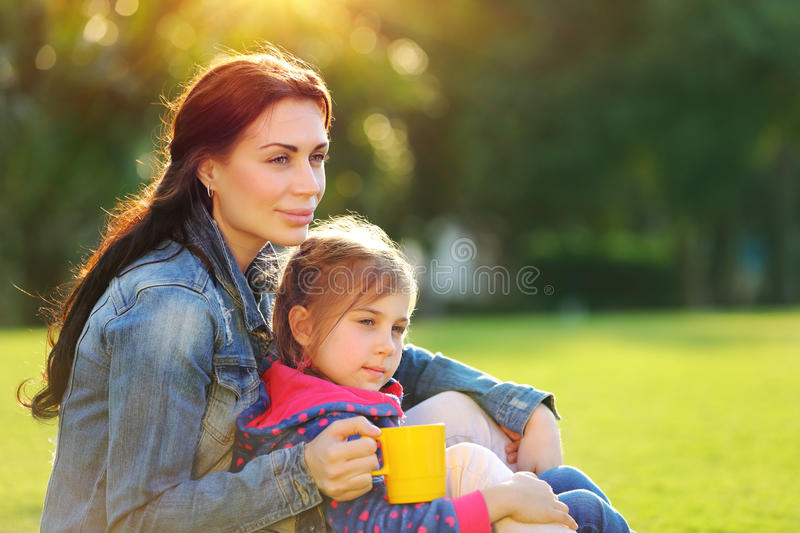 Happy family life. Portrait of a beautiful young mother with cute little daughter relaxing outdoors, drinking tea in the morning, with pleasure spending time stock photography