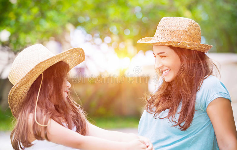 Happy family life. Portrait of a joyful young mother with her cute cheerful daughter wearing same straw hats and playing outdoors, laughing and looking on each stock image