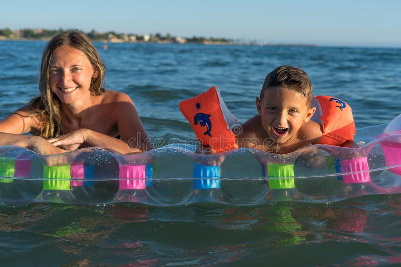 Happy family lifestyle.  Smiling young mother and son jumping and splashing with fun in breaking waves royalty free stock photo