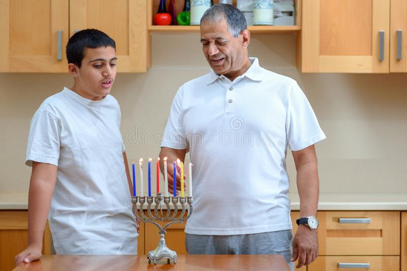 Happy family is lighting a candle celebrating together Jewish holiday Hanukkah. stock image