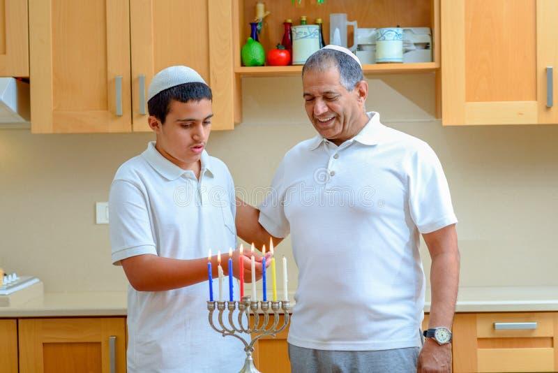 Jewish holiday Hanukkah. Jewish Dad and teenager son lighting Chanukkah Candles in a menorah for the holdiay royalty free stock image