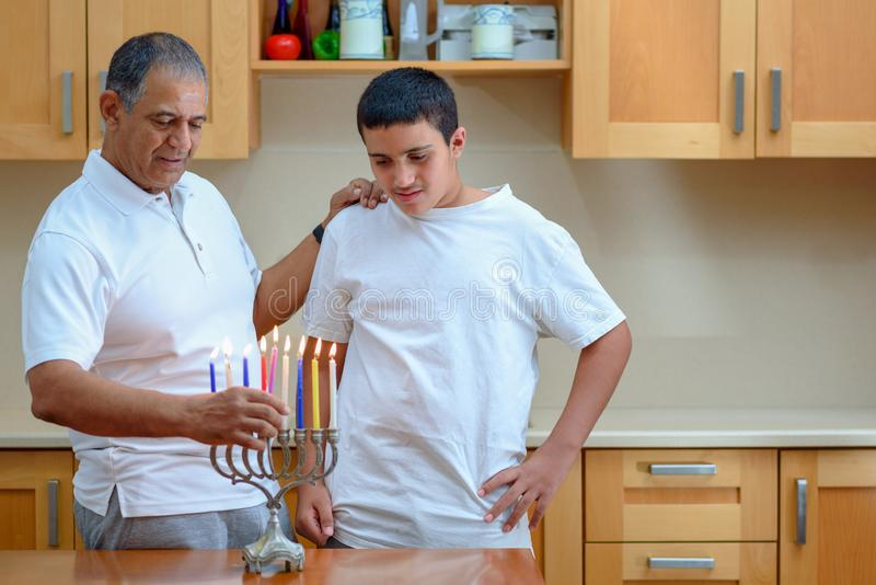 Happy family is lighting a candle celebrating together Jewish holiday Hanukkah. stock images