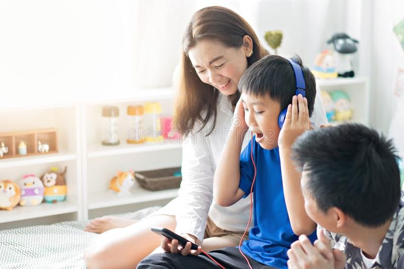 Happy family listening to music on bed in bedroom royalty free stock photography