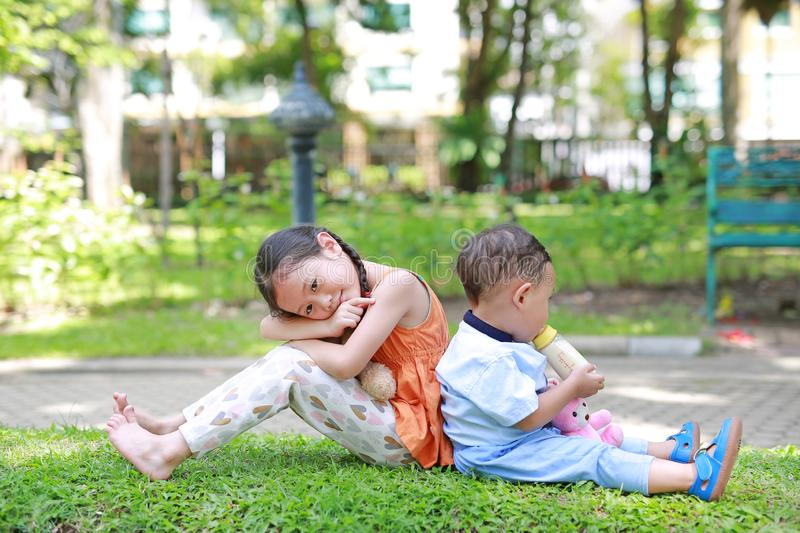 Happy Family. Little Asian sister and her younger brother sit back and lean back together in the green garden. Child girl cuddle. Teddy bear doll and boy Suck royalty free stock images