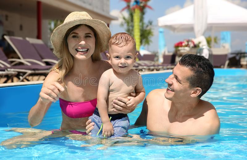 Happy family with little child relaxing in outdoor pool stock photo