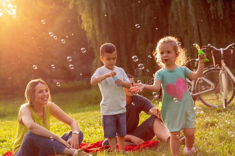 Happy family with children blow soap bubbles in park. Happy family with little children blow soap bubbles in park royalty free stock photo