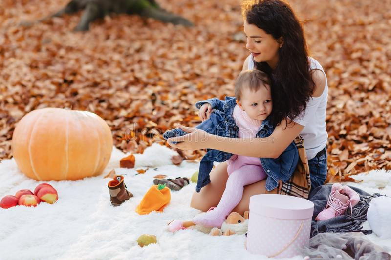 Happy family with little cute child in park on yellow leaf with. Happy stylish family with little cute child in park on yellow leaf with big pumpkin in autumn stock image