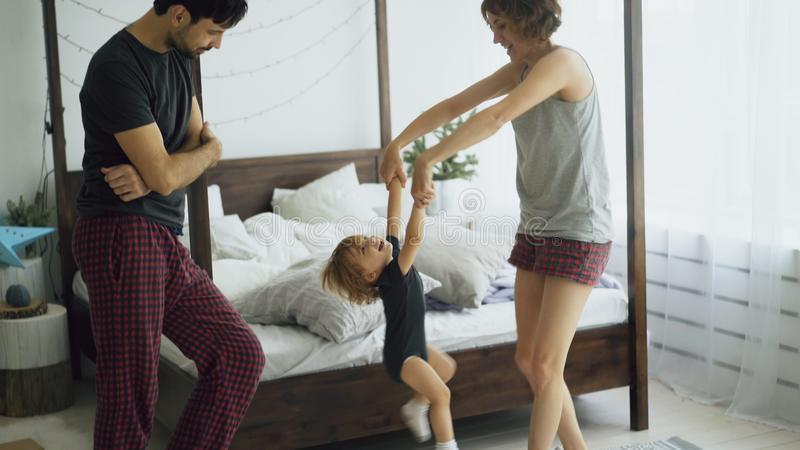 Happy family and little cute daughter dancing and turning around near bed in bedroom at home. In the morning stock photo