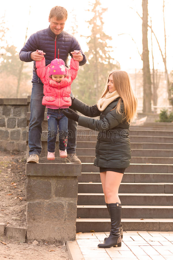 Happy Family with Little Daughter on Walk in Park stock photo