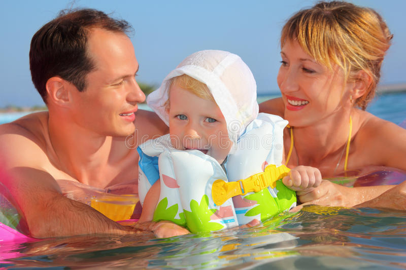 Happy family with little girl bathing in pool