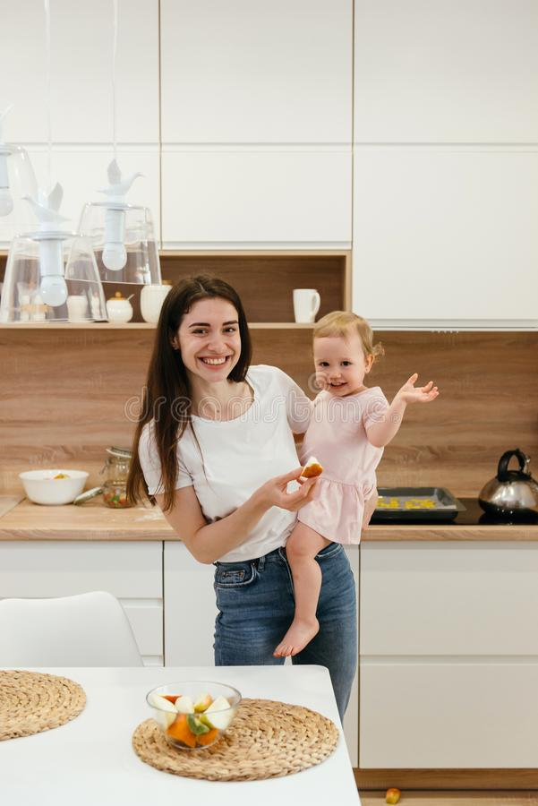 Happy family with little girl on the home kitchen before having breakfast, fresh fruits royalty free stock photo