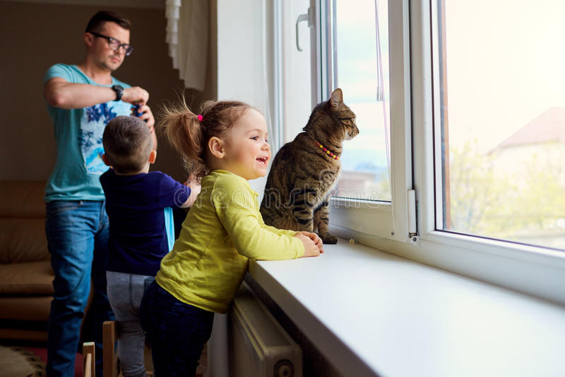 A happy family. Little girl looks out the window on background royalty free stock image