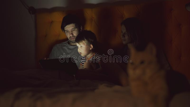 Happy family with little son learning to play tablet computer lying in bed with cat at home royalty free stock images
