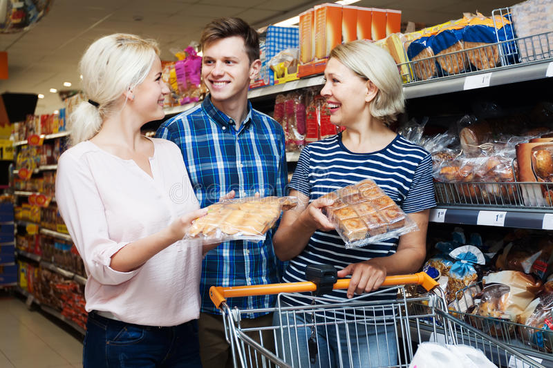 Happy family looking at assortment of pastry stock photography