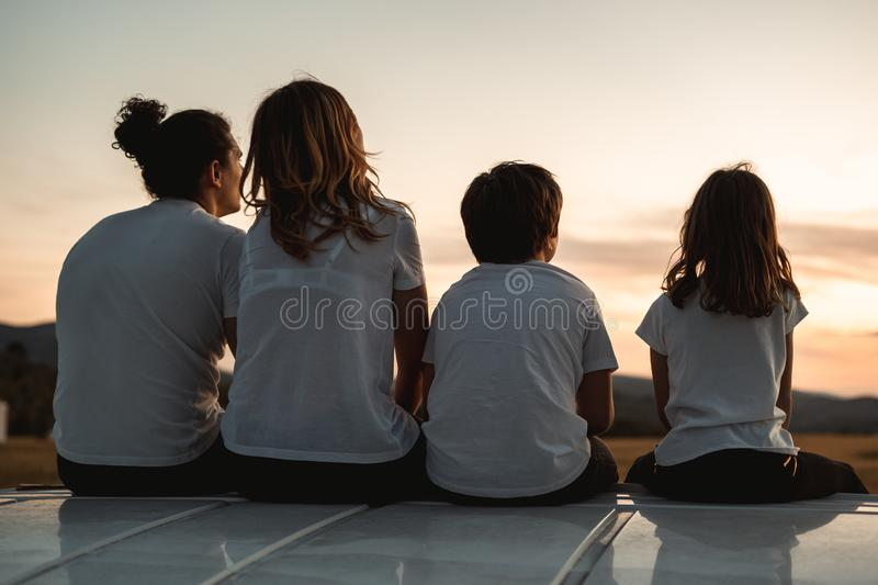Happy family looking at the sunset in the field. Family pointing to the horizon royalty free stock images