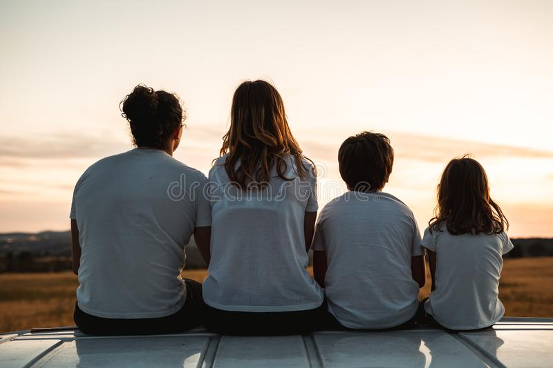 Happy family looking at the sunset in the field. Family pointing to the horizon stock photography