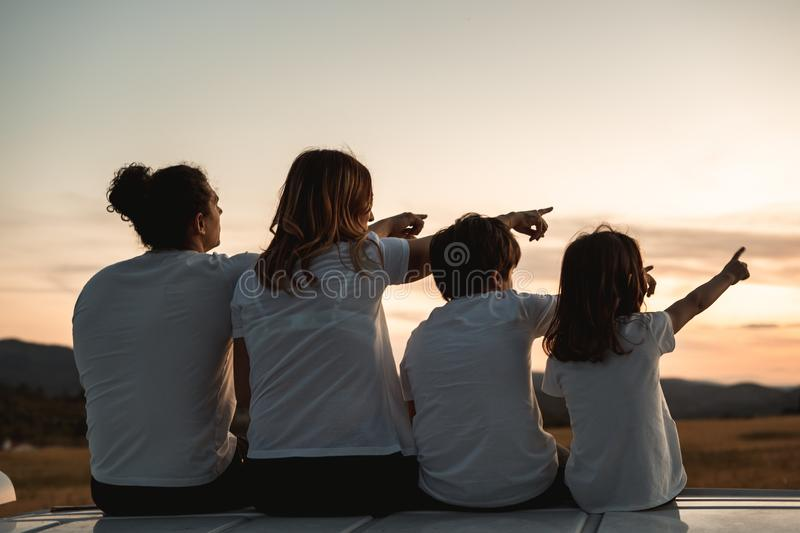 Happy family looking at the sunset in the field. Family pointing to the horizon royalty free stock image
