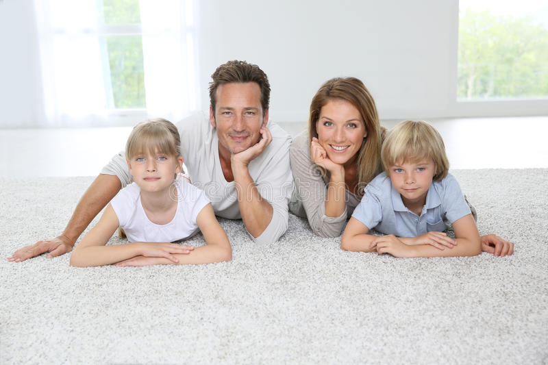 Happy family lying on carpet at home royalty free stock photo
