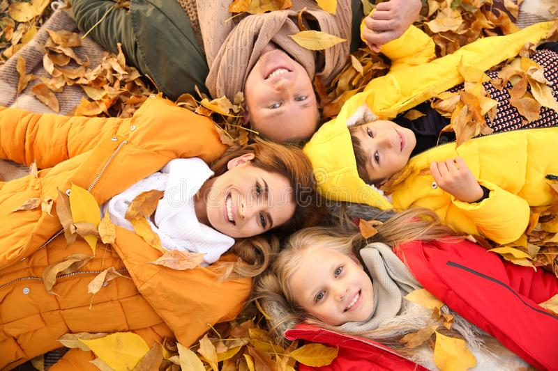 Happy family lying on dry leaves in autumn park stock photography