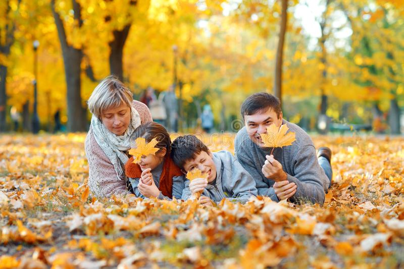 Happy family lying on fallen leaves, playing and having fun in autumn city park. Children and parents together having a nice day. stock images