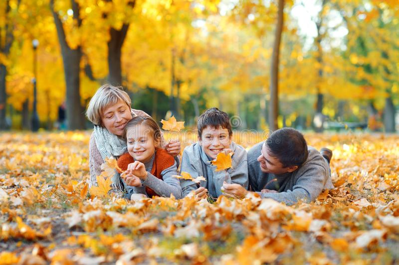 Happy family lying on fallen leaves, playing and having fun in autumn city park. Children and parents together having a nice day. stock photography