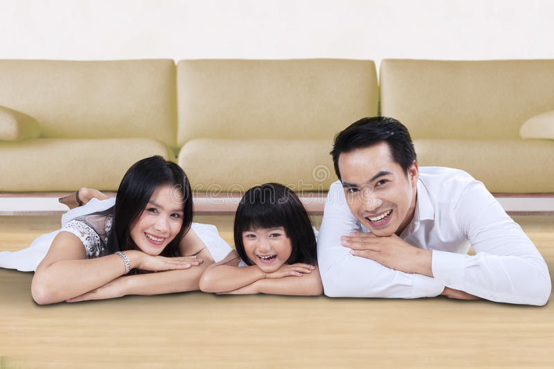 Happy family lying on the floor near the sofa stock photography