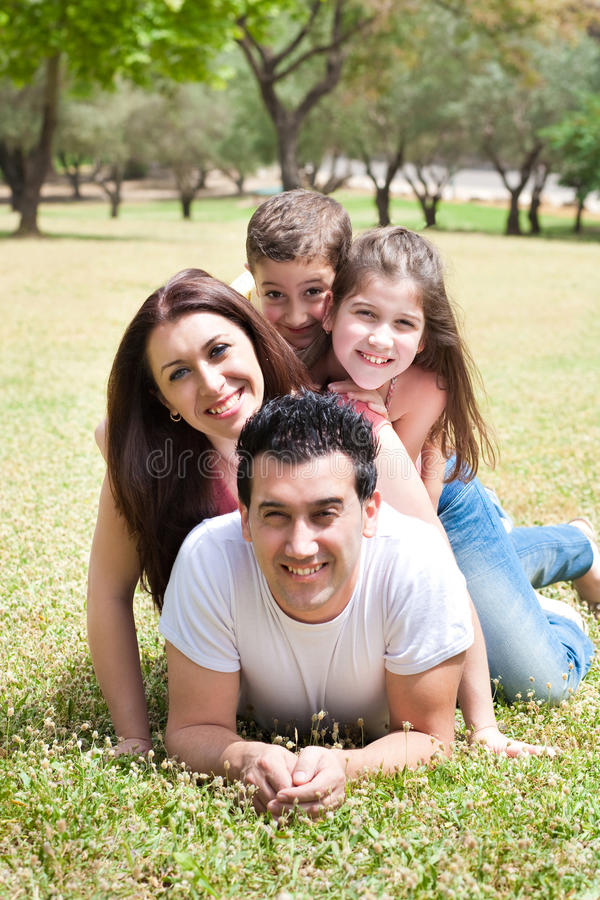 Happy family lying in the grass field at the park stock images