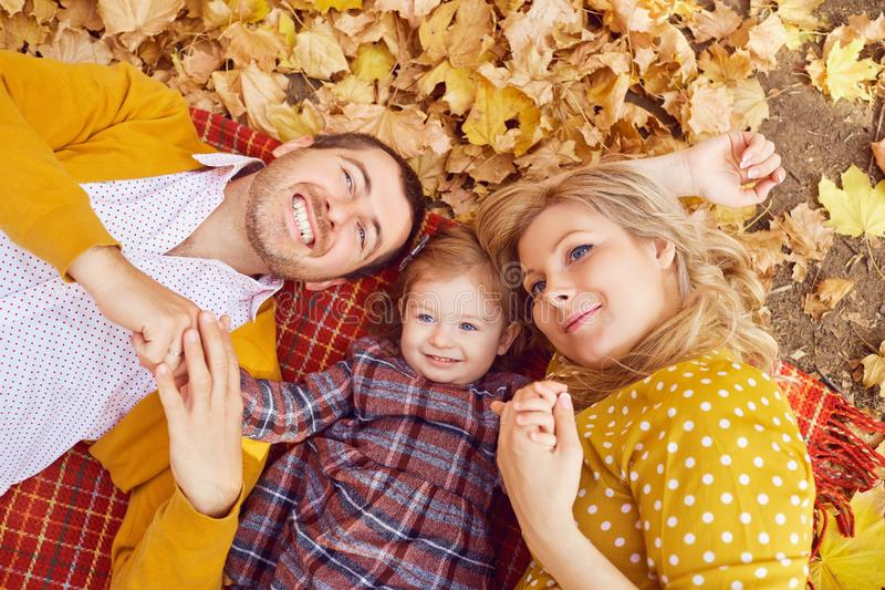 Happy family lying in the park in autumn. stock photography