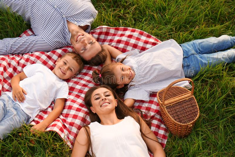 Happy family lying on picnic blanket in park stock photography