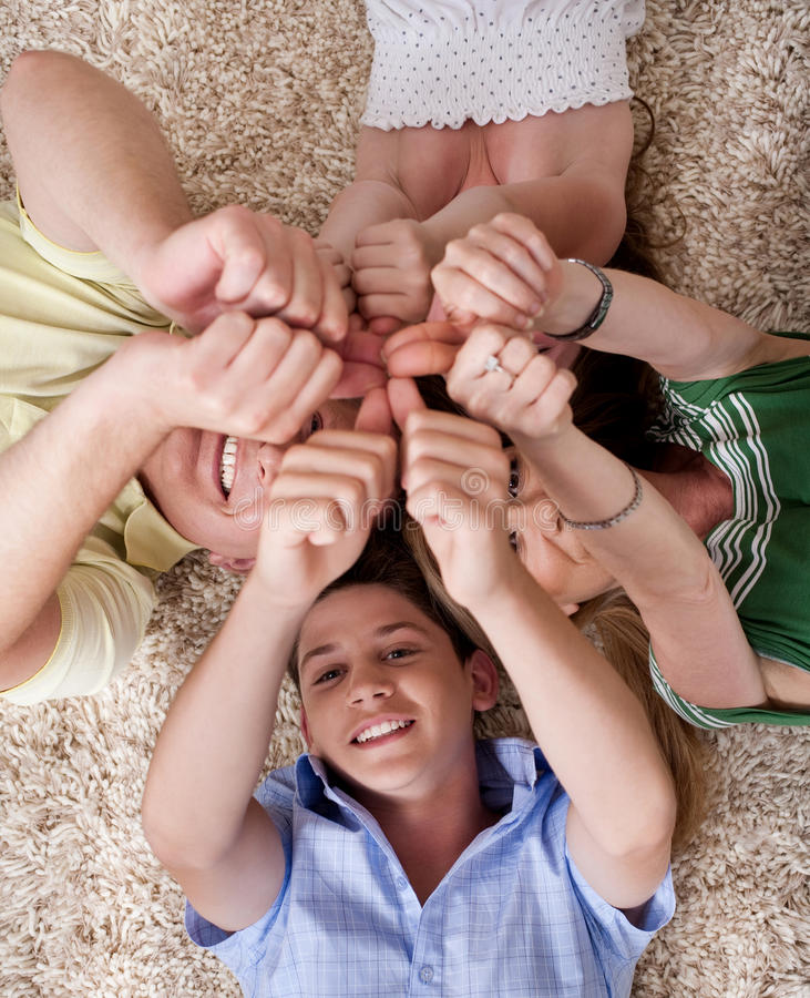 Happy family lying and showing thumps up together stock photos