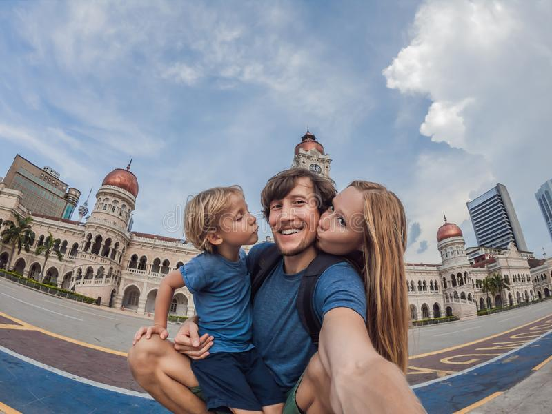 Happy family makes selfie on the background on background of Merdeka square and Sultan Abdul Samad Building. Traveling royalty free stock image