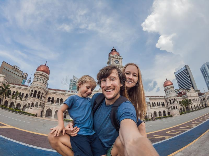 Happy family makes selfie on the background on background of Merdeka square and Sultan Abdul Samad Building. Traveling. Happy family makes selfie on background royalty free stock photos