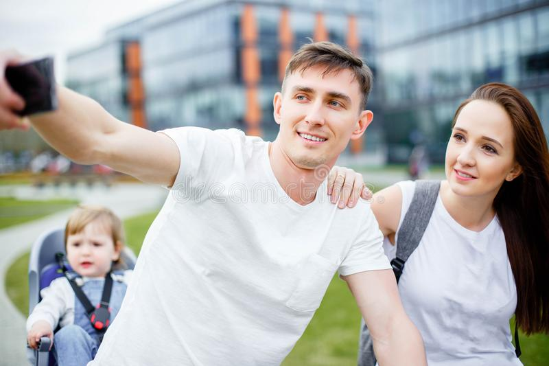 A happy family makes selfie on a smartphone while walking on bicycles in the summer. royalty free stock images