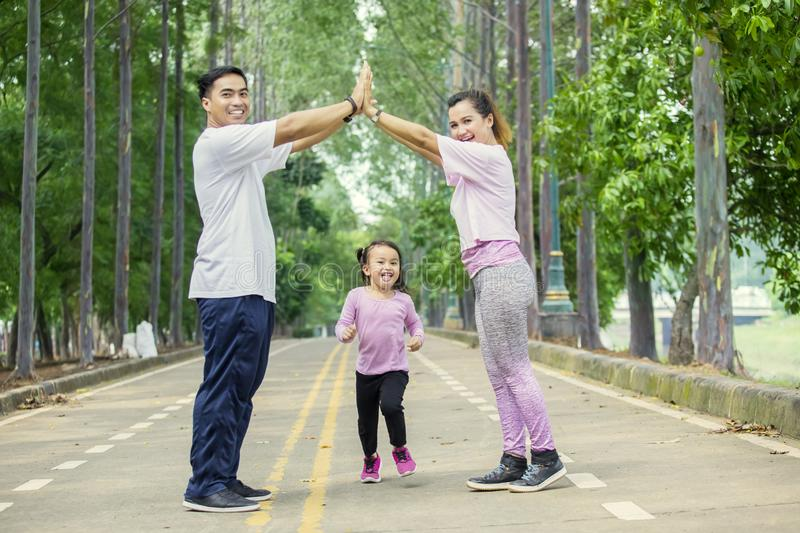 Happy family making house symbol in the park. Picture of Asian family looks happy while making house symbol in the park royalty free stock image