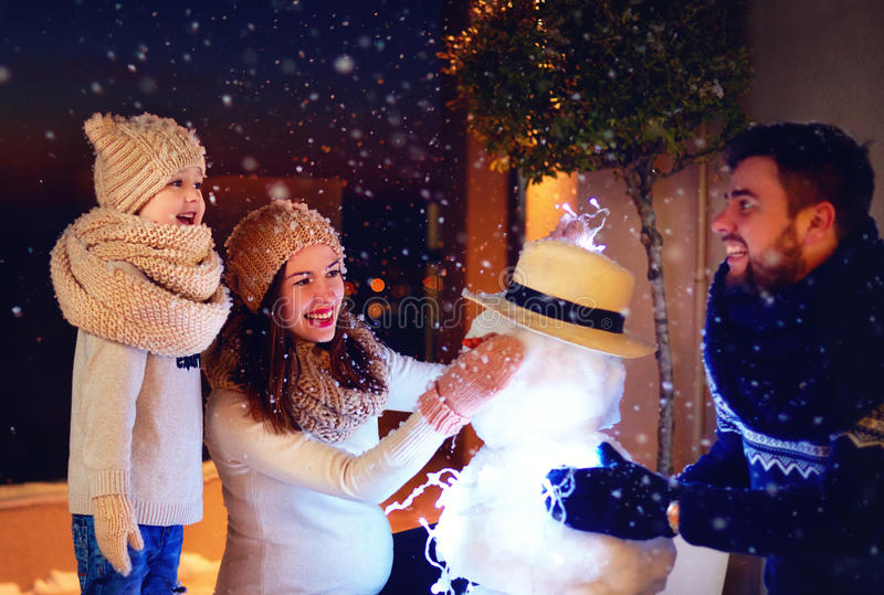 Happy family making snowman in evening light under winter snow royalty free stock photography