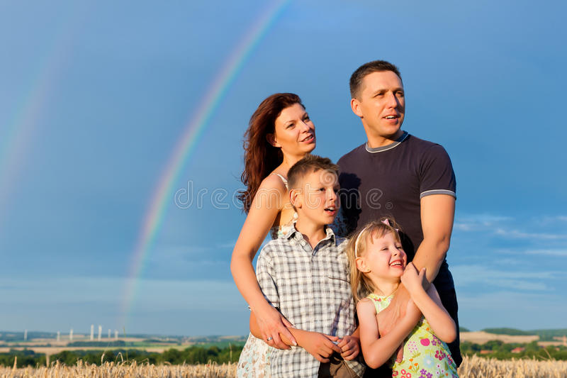 Happy family on a meadow in front of rainbow