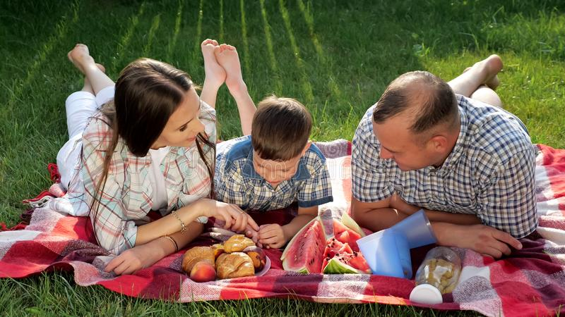 Happy family members lie on stomach on red blanket at picnic royalty free stock photography