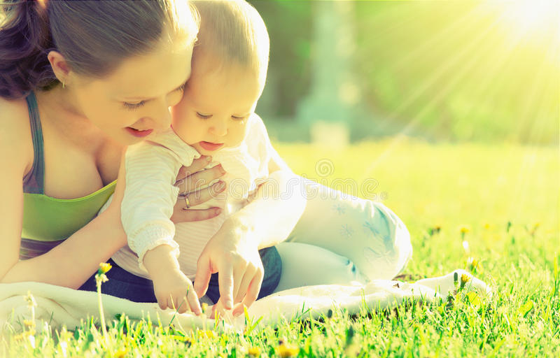 Happy family. Mom and baby in a meadow in the summer in the park royalty free stock image