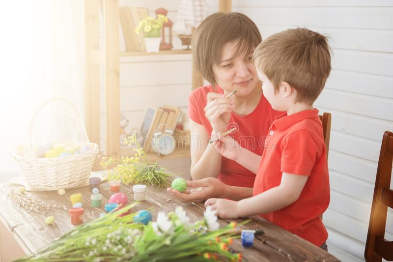 Happy family Mom and children son paint easter eggs with colors. Preparation for holiday royalty free stock images