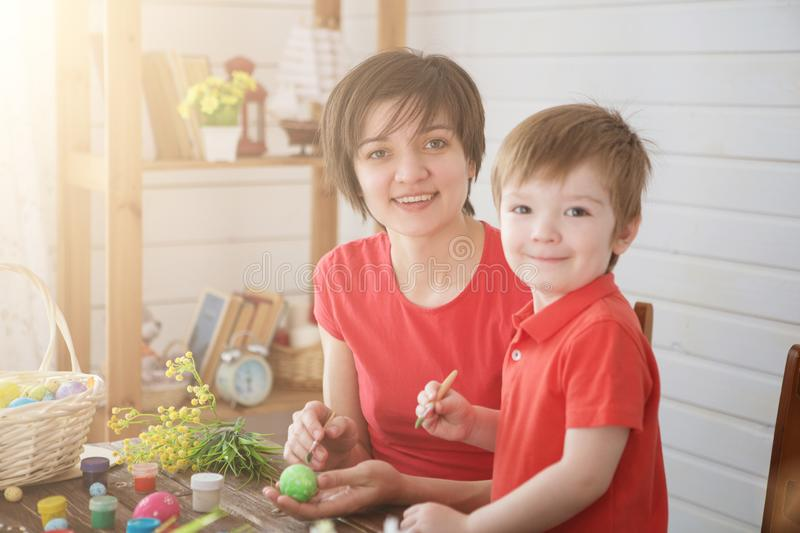 Happy family Mom and children son paint easter eggs with colors. Preparation for holiday royalty free stock photos