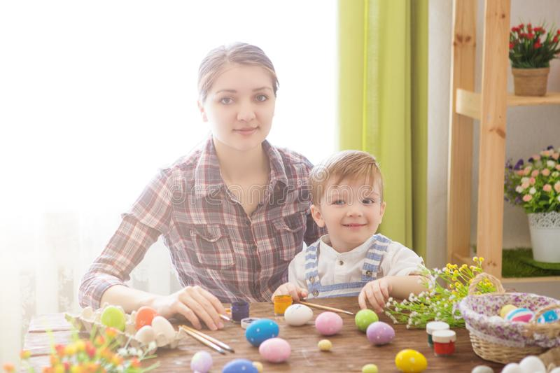 Happy family Mom and children son paint easter eggs with colors. Preparation for holiday stock photos