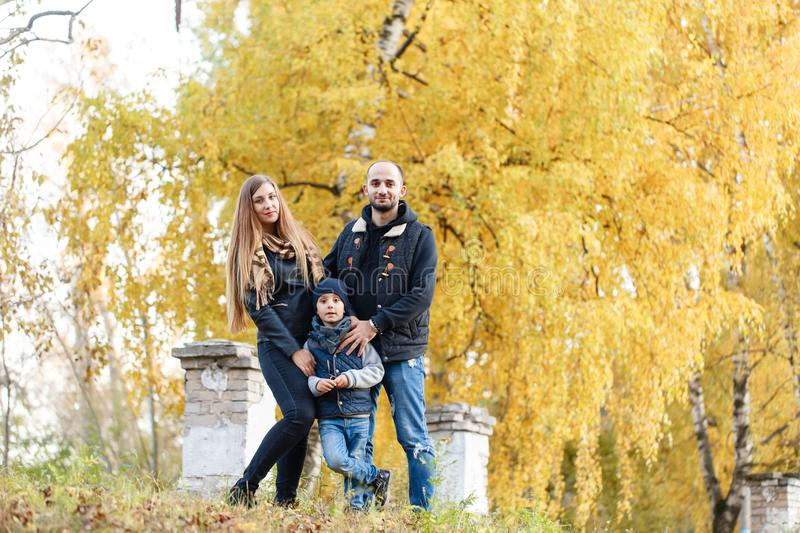 Happy family, mom and dad embrace his son in the park. Walk of Bright autumn day. Trees with yellow foliage. Warm royalty free stock images