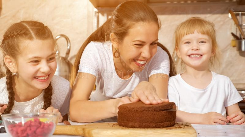 Happy family mom and daughters are cooking birthday cake together. royalty free stock photos
