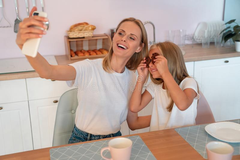Happy family. Mom and her cute little daughter are having fun making selfie holding chocolate chip cookies as eyes and smiling stock images
