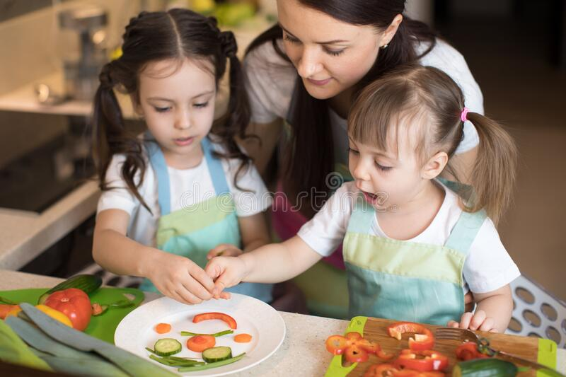 Happy family mom and her little daughters are preparing healthy food, they make smiley face with vegetables morsels in royalty free stock images
