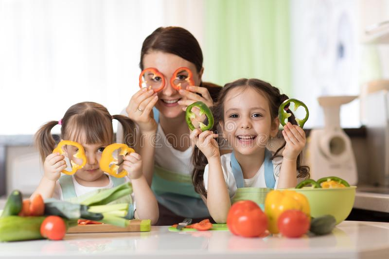 Happy family mother and kids having fun with food vegetables at kitchen holds pepper before their eyes like in glasses. Happy family mom and kids having fun with stock images