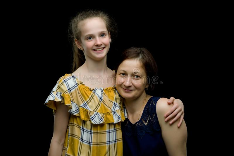 Mom and little daughter studio portrait.On black background stock photography