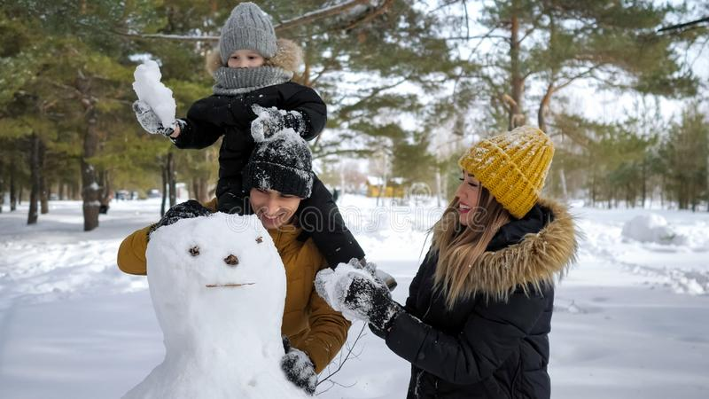 Young family, mom, son and dad are building a snowman in winter city park. stock images